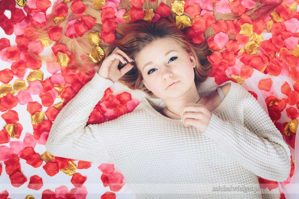 sesja w płatkach róż w stylu American Beauty, dziewczyna w płatkach róż